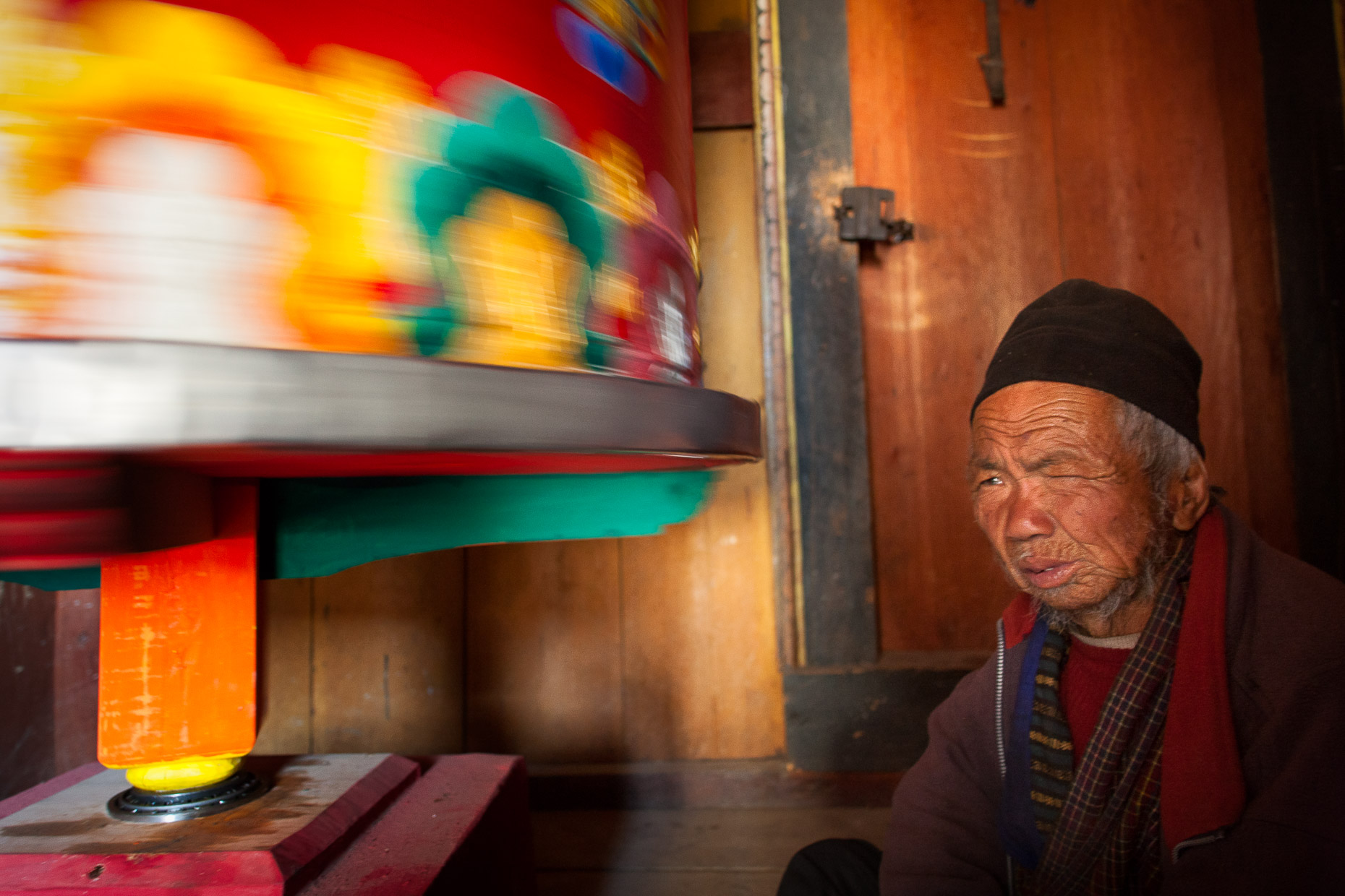 Old man at prayer wheel, Ugyen Choling, central Bhutan